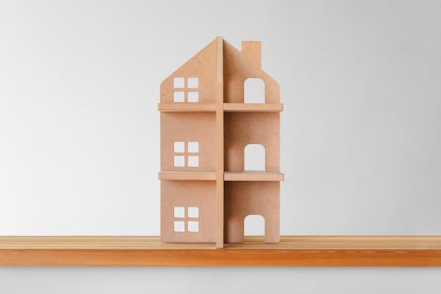 木製の棚の上のおもちゃの木造住宅。不動産のシンボル