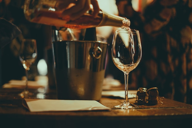 ワインの試飲:木製のテーブルの上にシャンパンのボトルでワインを冷却するための銀製のバケツ