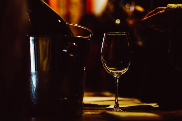 照らされたガラスは冷却のためのバケツの中のワインの瓶の隣のテーブルにあります。ローキー
