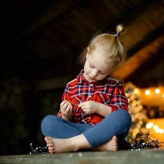 クリスマスに装飾された狩猟家に座っているチョコレートの卵を食べるかわいい幼児の女の子。クリスマスの朝の概念。肖像画を閉じます。