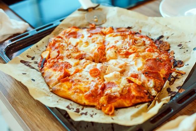 オーブンの外にあるベーキングシートの上のベーキングシートに自家製ピザを調理した。おいしい自家製イタリアンスナック。