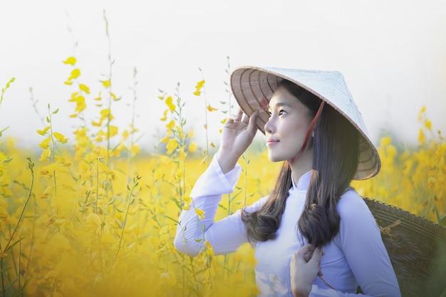 Вьетнамская девушка с желтыми цветами.