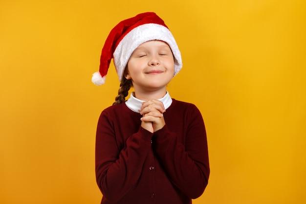 Маленькая девочка загадывает желание на рождество.
