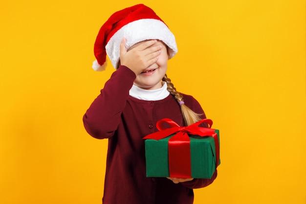 Маленькая девочка держит коробку с подарком и закрыла глаза рукой.