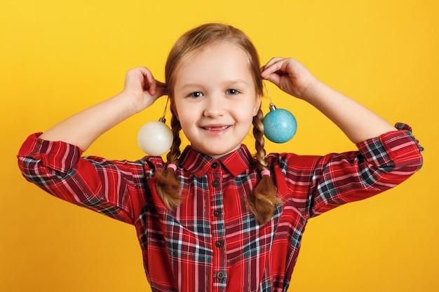 耳の近くのクリスマスボールのおもちゃを持つ少女。