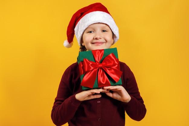 Ребенок держит подарок под головой в рождественской шапке