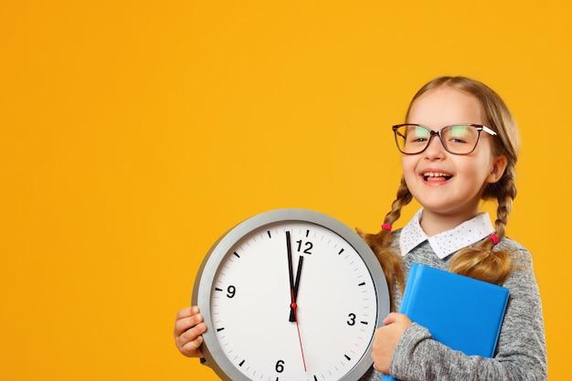 Портрет улыбающегося маленькая девочка в очках с книгой и часами.