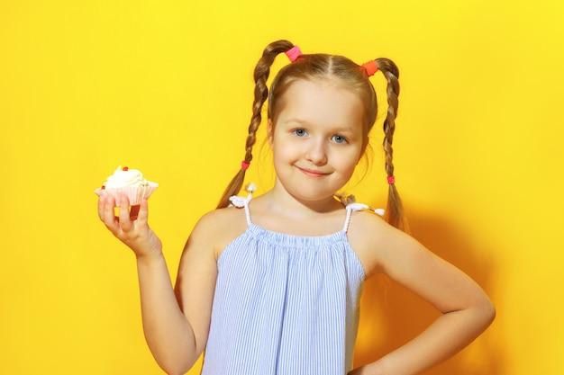 小さな女の子はケーキを持っています。