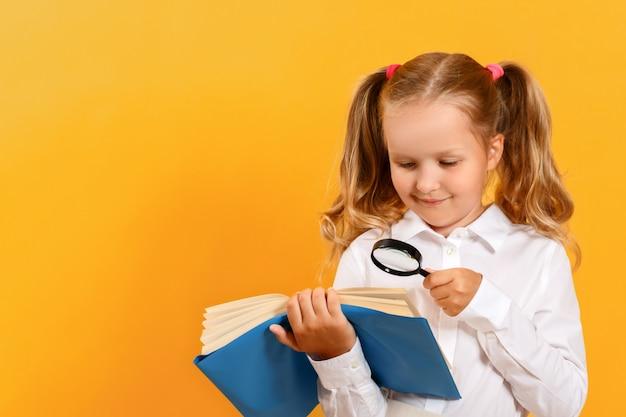 小さな女の子は、黄色の背景に虫眼鏡でテーブルの上の本を読んでいます。