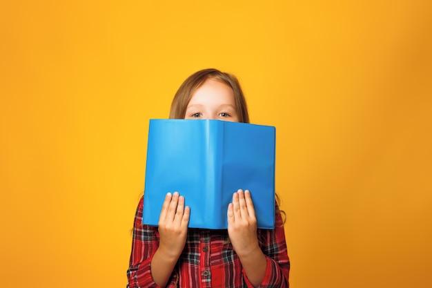 小さな女の子が開いた本の後ろに隠れています