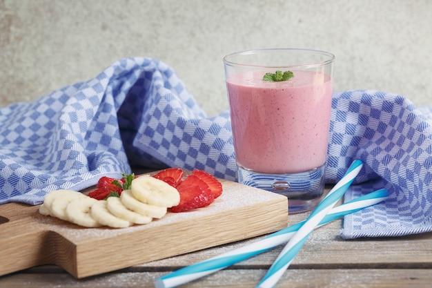 おいしいイチゴとバナナのスムージー、または牛乳を新鮮な果実と一緒に振る。