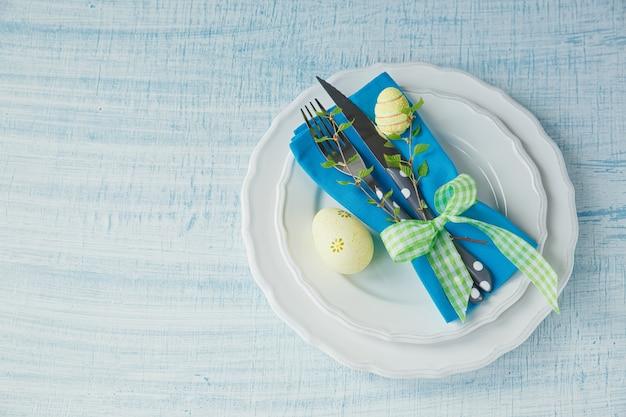 塗装卵とカトラリー水色の木製の背景にイースターテーブルの設定