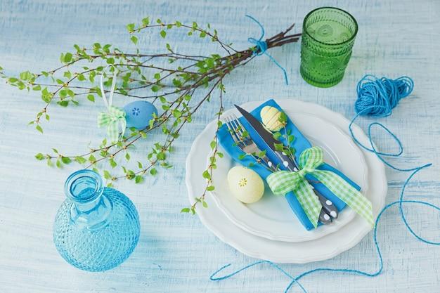 塗装卵とカトラリー青い木製の背景とイースターテーブルの設定