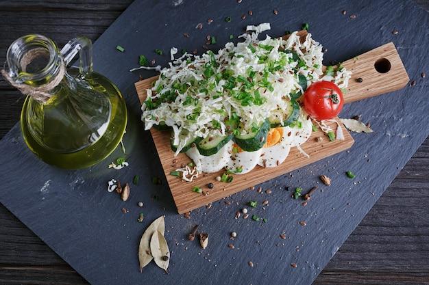 健康食品とトマト、キュウリ、キャベツ、ネギ、卵、スパイス、暗闇の中で食材