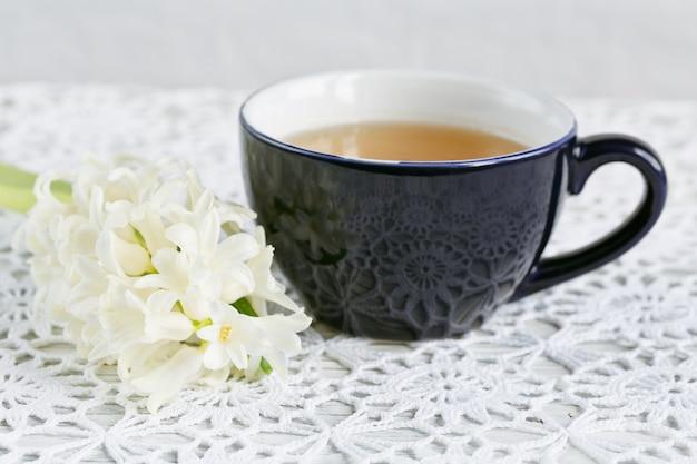 Чашка зеленого чая, цвет макарун и белых цветов