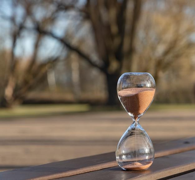 春の公園のベンチに砂時計。