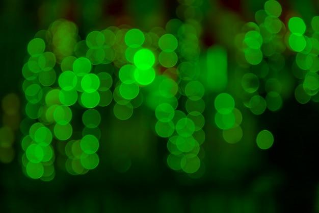 ランタンライトと花輪でデフォーカスしたマルチカラー。緑のボケとぼかし効果。デフォーカス。クリスマス、新年、その他のホリデー気分。