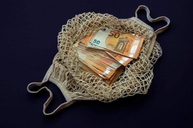 Большое количество евро в многоразовой хлопчатобумажной сетке на темно-синем фоне.