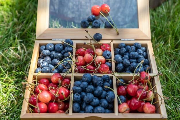 Большая коробка полна черники и вишни