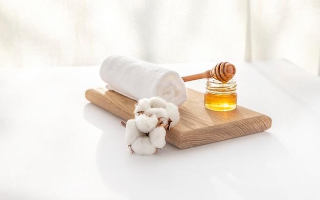 柔らかな白いタオル、綿の花、蜂蜜のバックライト。スパでの蜂蜜トリートメント。スパ、純粋さ、調和のコンセプト。