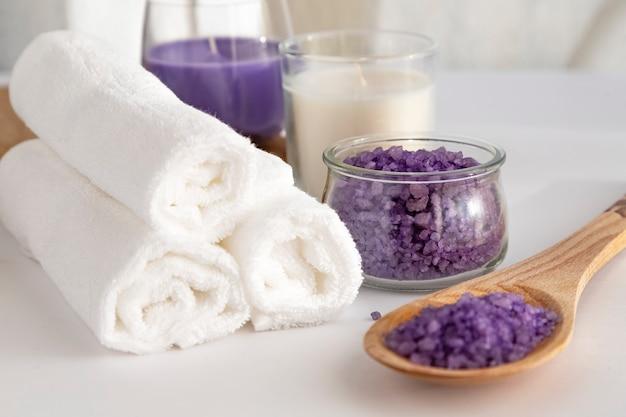Белые полотенца сложены в рулон на белом фоне, бело-сиреневая свеча, соль для скрабов и запах лаванды. концепция спа. концепция чистоты.