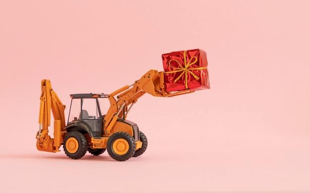 おもちゃの掘削機は、弓で結ばれたギフトボックスを運ぶ。ピンクの背景。コピースペース、