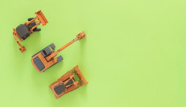 おもちゃは前部積込み機、鉱山の掘削機およびブルドーザーを模倣します。緑の背景。コピースペース。