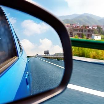 車のバックミラーと高速道路