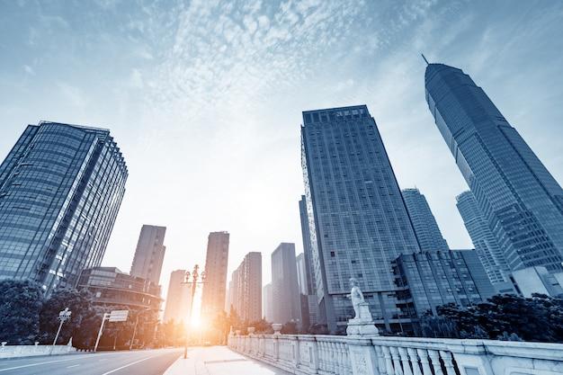 高層ビルと夕日が見える道路