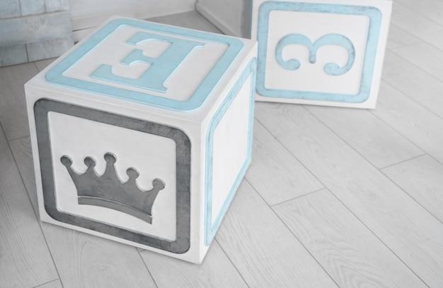 木製の床で子供のためのアルファベットの木製キューブ