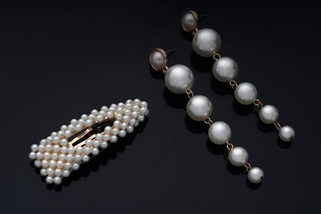 真珠のイヤリングと黒い背景のヘアピン