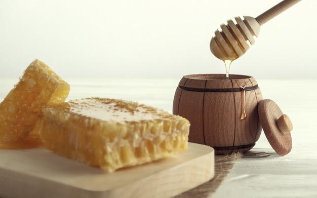 木製の瓶にハニーディッパー、木製トレイにハニーコーム