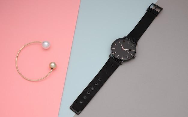 Черные наручные часы и золотой жемчужный браслет на стене в пастельных тонах
