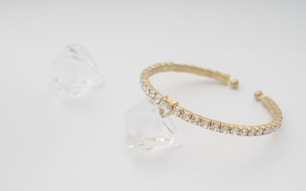 白い壁にゴールドとダイヤモンドのハート型ブレスレット
