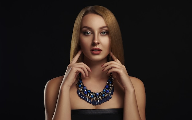 Портрет красивой девушки с прямыми блестящими волосами в голубом ожерелье
