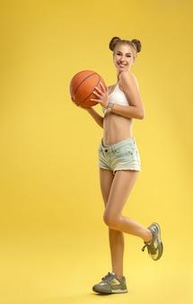 黄色の壁にバスケットボールを保持しているジーンズのショートパンツを着て幸せな興奮している女の子