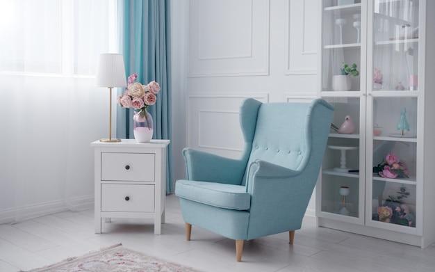 Синее классическое кресло и белая тумба с настольной лампой и вазой с цветами в белой комнате