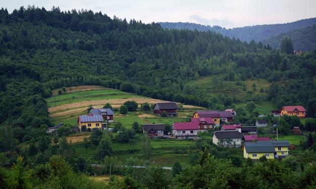 ウクライナの田舎の太陽電池パネルのある家-山の小さな村の家のビュー