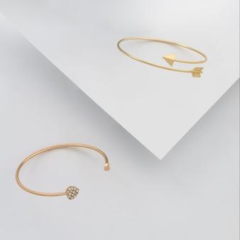 Форма сердца и стрелка формы золотые браслеты на фоне белой бумаги