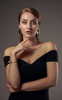 Вертикальный студийный снимок красивой девушки с естественным оттенком макияжа с плеча черное платье на сером фоне
