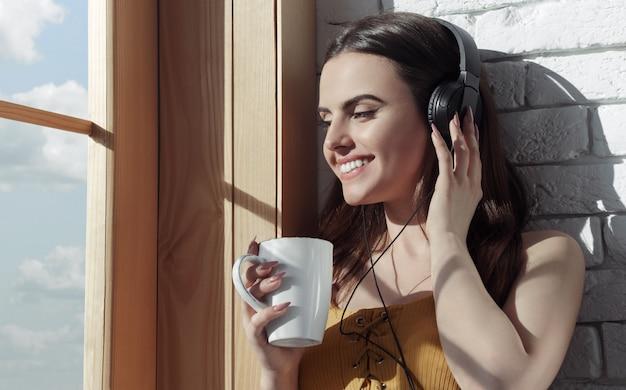 Молодая девушка слушает музыку и во время пить кофе у окна на утро