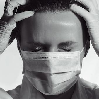 マスクを着用し、痛みのため目を閉じている医療従事者の黒と白の肖像画
