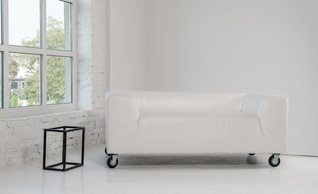 白い明るい部屋で白い革のソファ