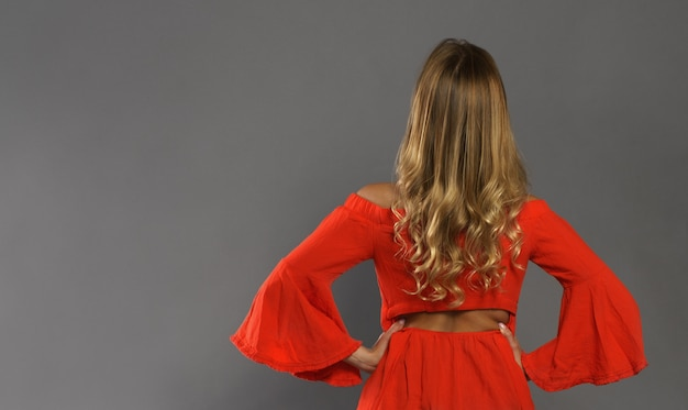 楽しみにして後ろから見るオレンジ色のドレスを着ている金髪の大人の女性