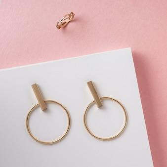 Взгляд сверху современной пары золотых серег и кольца на розовой и белой поверхности