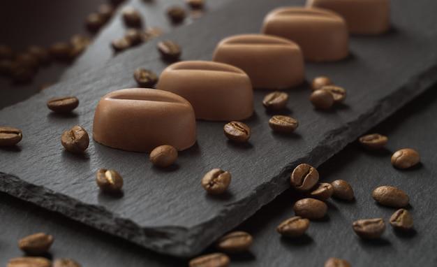 Кусочки шоколада в форме кофейных зерен и кофейные зерна на темных каменных плитах