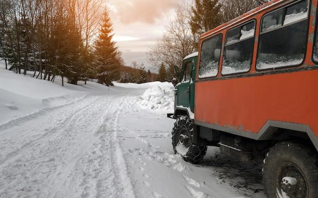 雪のチェーンホイールとオレンジ色の古い旅客トラック