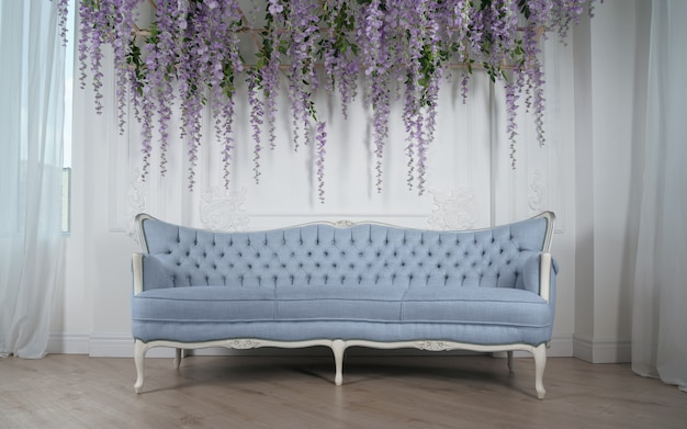 天井から絞首刑にされた紫色の花の下でフランスの古典的な青いソファ