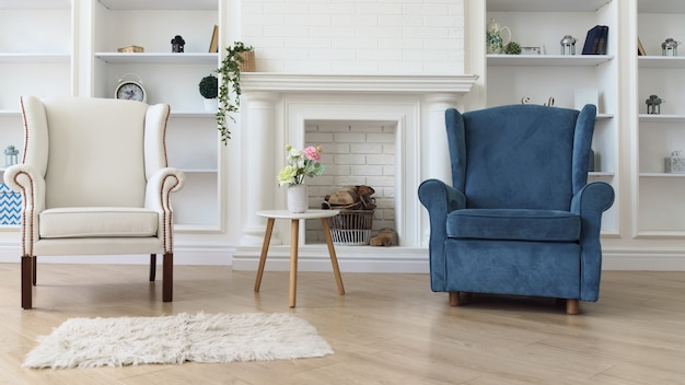 リビングルームの暖炉の前で白いモダンなテーブルと白と青のアームチェア