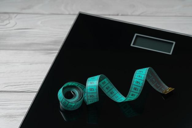 木製の背景にデジタルバスルーム体重計にグリーン定規テープ